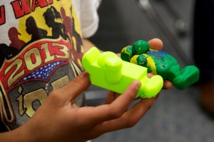 Boy holding clay model and 3D printed model