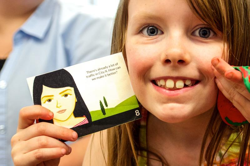 A third grader holds up her City X citizen card.